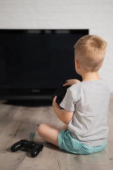 Garotinho em casa jogando jogos digitais