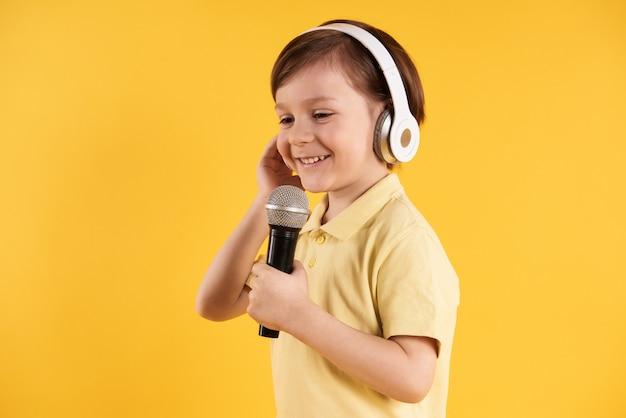 Garotinho em fones de ouvido canta no karaoke.