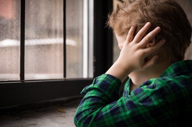 Garotinho em pé perto de uma janela com um humor triste e fechando os ouvidos com as mãos