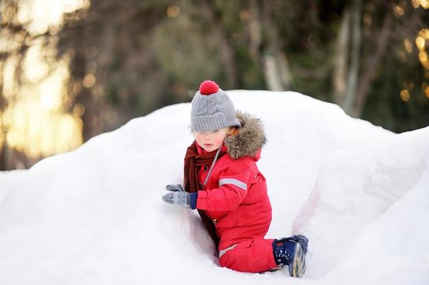 Garotinho em roupas de inverno vermelho se divertindo com neve fresca