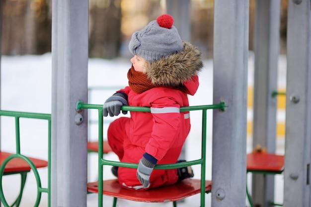 Garotinho em roupas de inverno vermelho se divertindo no playground ao ar livre