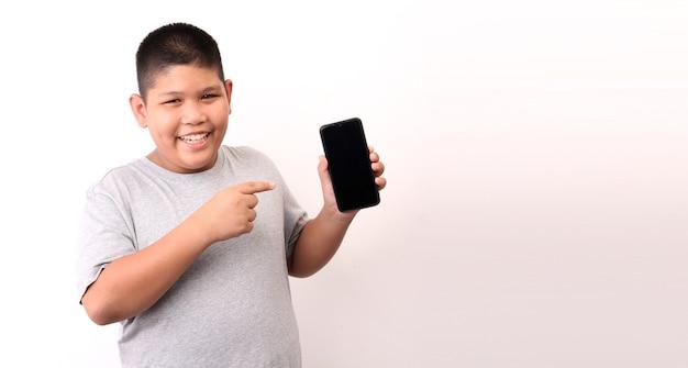 Garotinho em t-shirt apresentando telefone inteligente em fundo branco no estúdio.