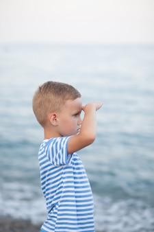 Garotinho em t-shirt listrada, brincando na praia com fundo desfocado pelo mar