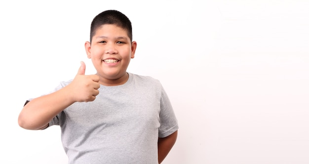 Garotinho em t-shirt mostrando o gesto de ok em fundo branco.