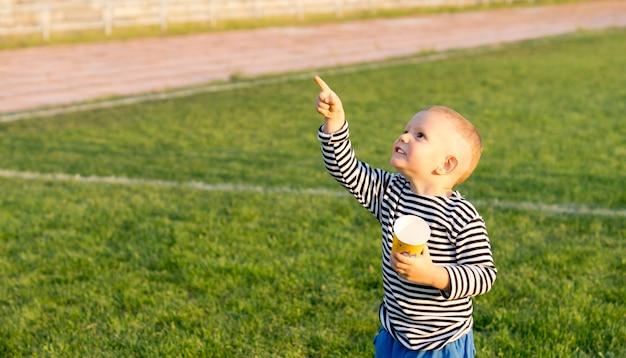 Garotinho em um campo de jogos verde com uma caneca na mão apontando para o céu