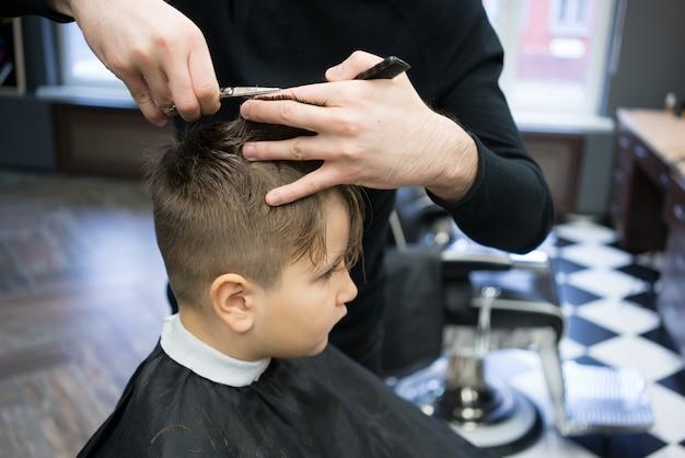 Garotinho em um corte de cabelo no barbeiro se senta em uma cadeira.
