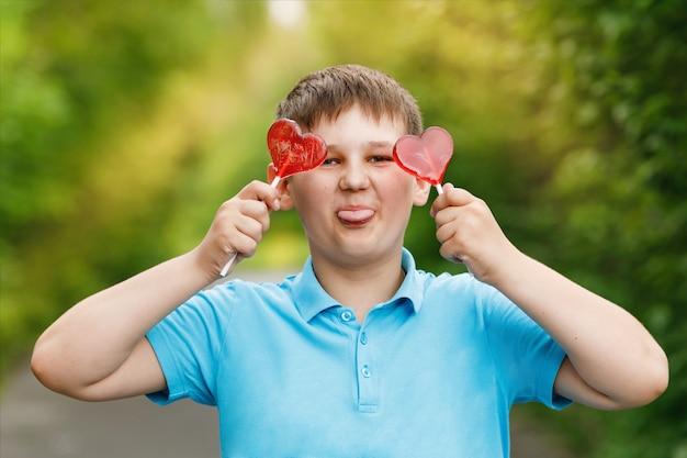 Garotinho em uma camiseta azul com pirulitos em forma de coração perto dos olhos, mostrando a língua.