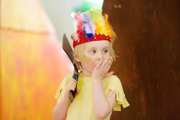 Garotinho envolvido no teatro infantil de performance studio no papel de índio americano.