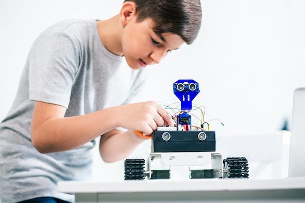 Garotinho esperto e concentrado construindo um robô enquanto aprimora suas habilidades de engenharia
