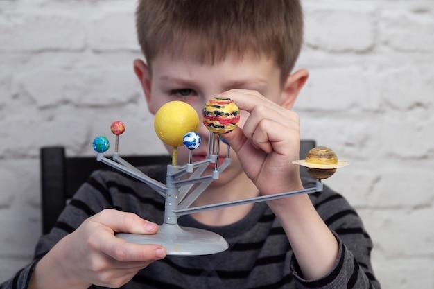 Garotinho está brincando com o modelo do sistema solar