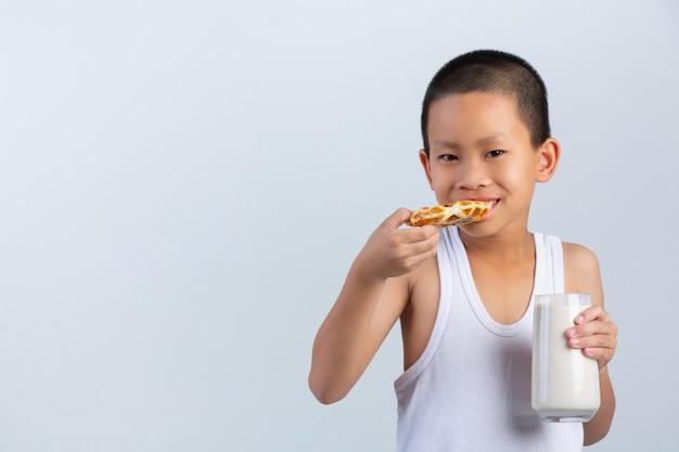 Garotinho está comendo waffles com copo de leite na parede branca.