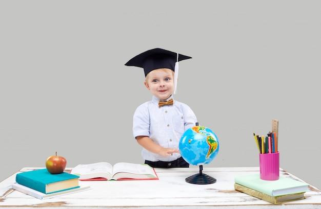 Garotinho está estudando enquanto usava um chapéu de formatura em uma parede cinza isolada