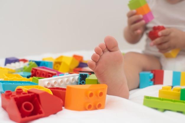 Garotinho está jogando o bloco colorido na cama branca