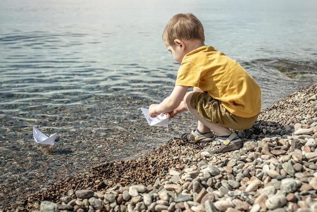 Garotinho está lançando barcos de papel branco nas águas claras de um grande lago com fundo pedregoso