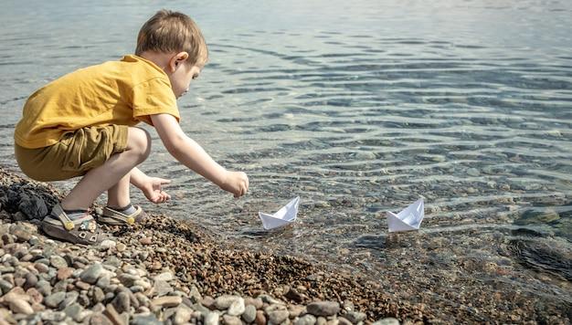 Garotinho está lançando barcos de papel branco nas águas cristalinas do mar