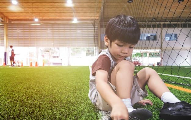 Garotinho está mudando os sapatos para treinamento de futebol