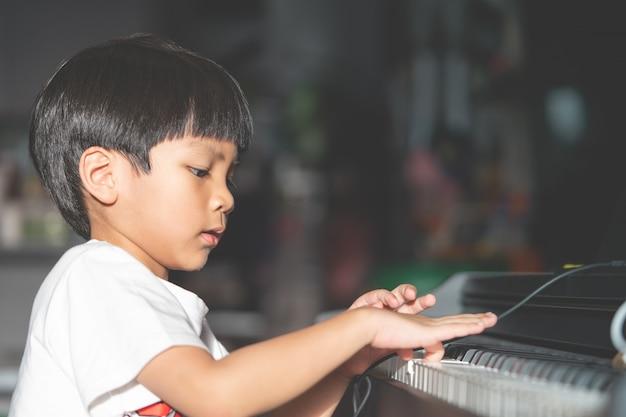 Garotinho está tocando com piano e music tablet em casa