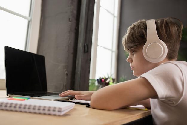 Garotinho, estudando por videochamada em grupo, usa videoconferência com o professor, ouvindo o curso online.