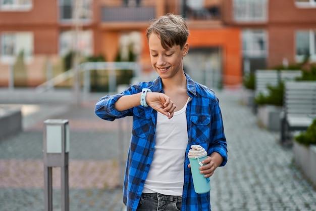 Garotinho falando por smartwatch azul e bebe chá perto da escola.