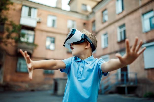 Garotinho fascinado usando óculos de realidade virtual vr. ao ar livre
