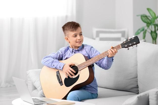 Garotinho fazendo aulas de música online em casa
