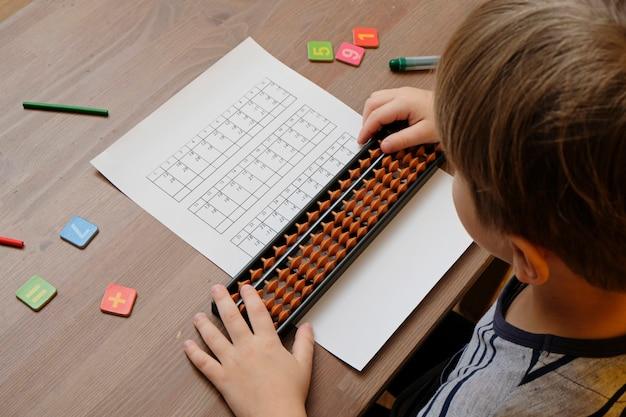 Garotinho fazendo exercícios de matemática simples com pontuações de ábaco. aritmética mental. vista do ombro
