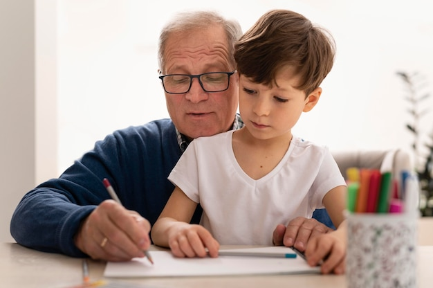 Garotinho fazendo lição de casa com a avó