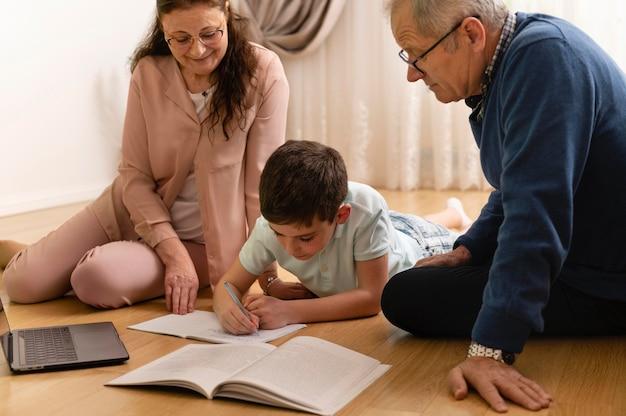 Garotinho fazendo lição de casa com os avós em casa