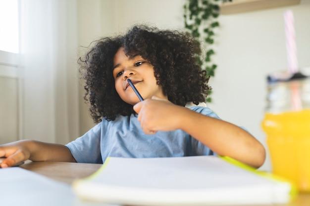 Garotinho fazendo lição de casa em casa segurando um lápis olhando para o laptop