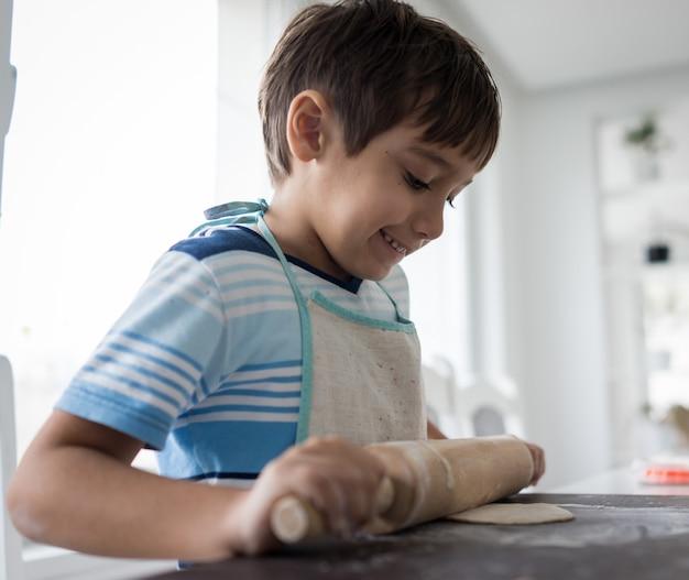Garotinho fazendo massa para delicioso doce