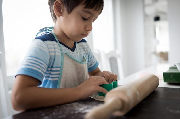 Garotinho fazendo massa para doce delicioso
