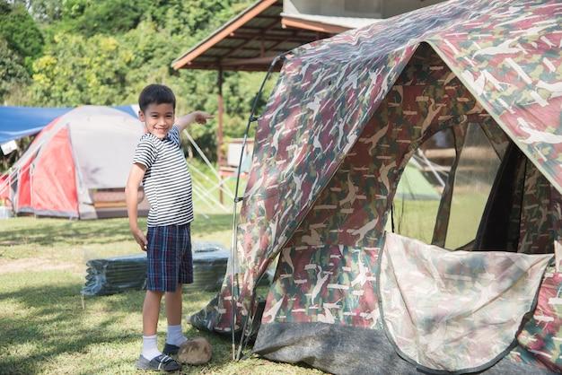 Garotinho fazendo uma tenda de acampamento atividade ao ar livre de horário de verão com a família