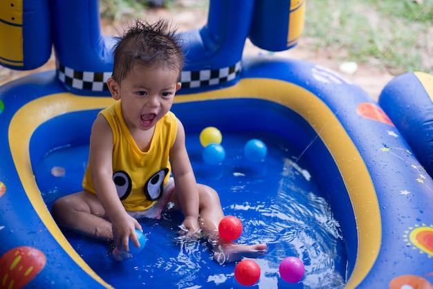 Garotinho feliz com piscina infantil