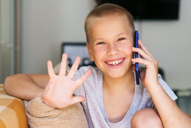 Garotinho feliz se divertindo jogando no celular criança pré-escolar sentada no sofá com um sorriso