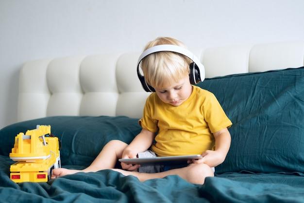 Garotinho feliz sorridente usando tablet em fones de ouvido sem fio na cama em casa
