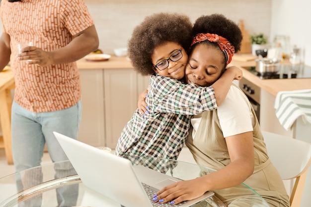 Garotinho fofo abraçando a mãe para fazer networking na frente do laptop