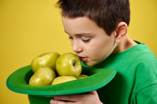 Garotinho fofo aprecia o cheiro de maçãs verdes em um boné de duende irlandês verde