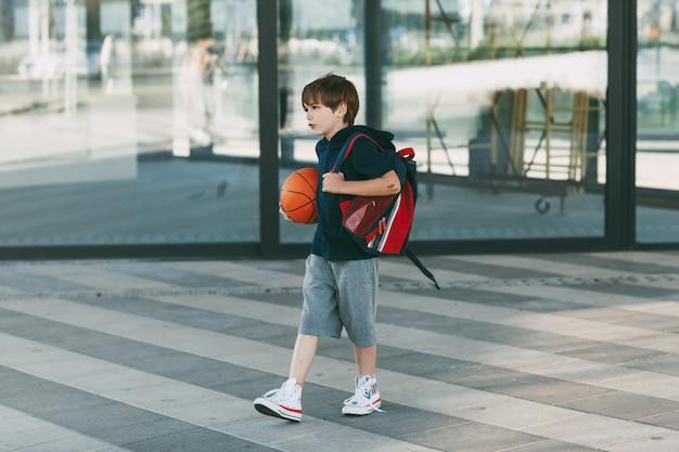 Garotinho fofo com uma bola de basquete