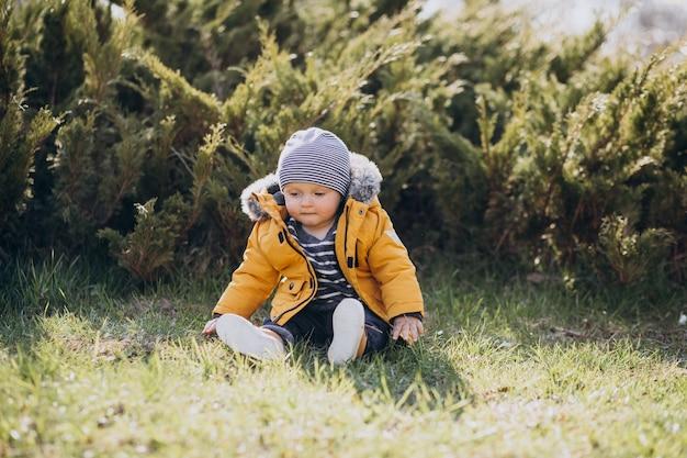 Garotinho fofo com uma jaqueta amarela no parque