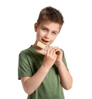 Garotinho fofo comendo chocolate com branco