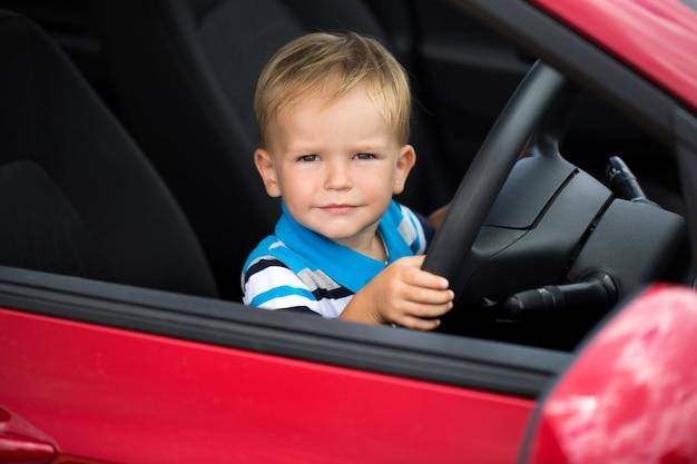 Garotinho fofo dirigindo o carro do pai