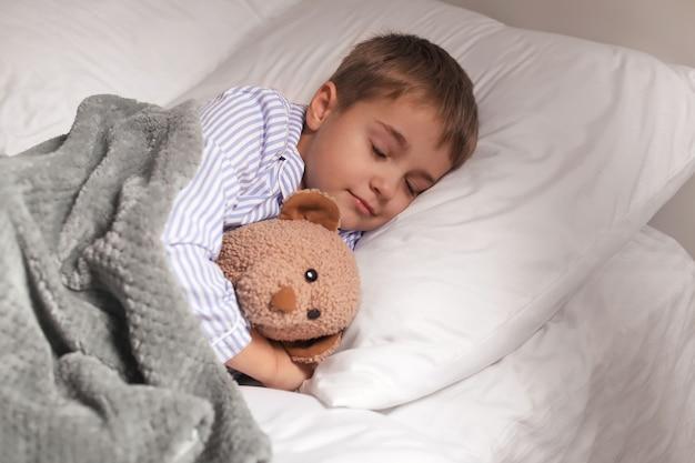 Garotinho fofo dormindo na cama