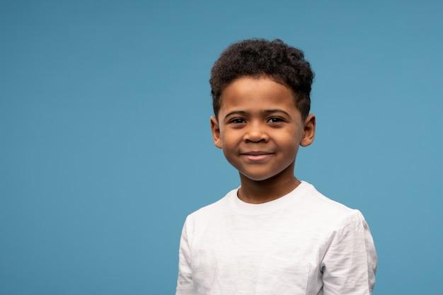Garotinho fofo e feliz de etnia africana em uma camiseta branca em azul