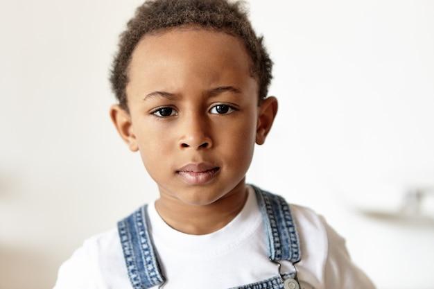 Garotinho fofo e rabugento de aparência africana vestido com macacão jeans e camiseta branca