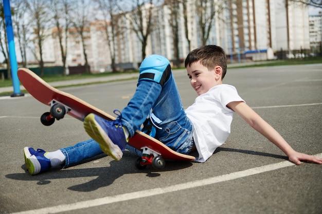Garotinho fofo escorregou e caiu do skate no asfalto do parquinho