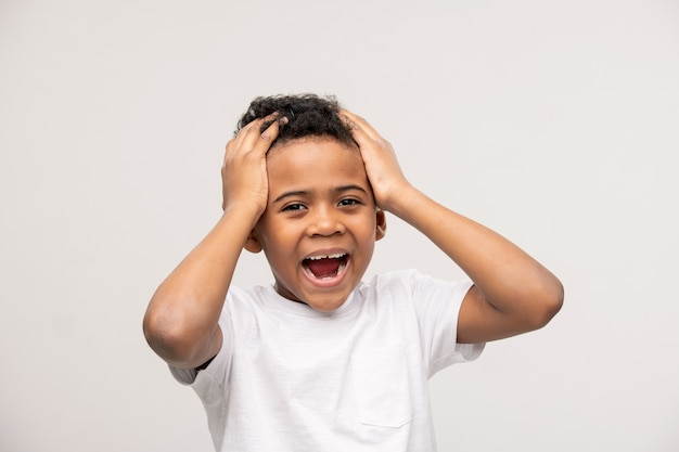 Garotinho fofo extremamente feliz tocando a cabeça com as mãos e gritando para expressar que está surpreso com uma boa notícia inesperada