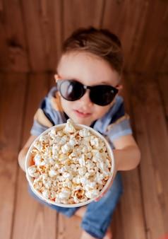 Garotinho fofo menino de 2 a 3 anos, óculos de cinema 3d imax segurando balde para pipoca