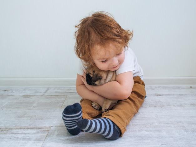 Garotinho fofo ruivo cacheado em uma camiseta branca com seu filhote de cachorro pug