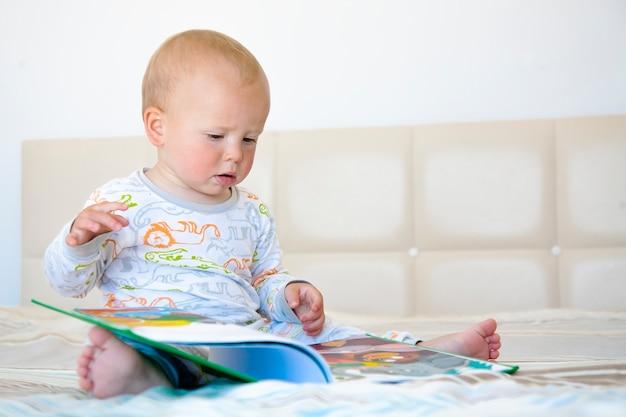 Garotinho fofo sentado na cama lendo um livro