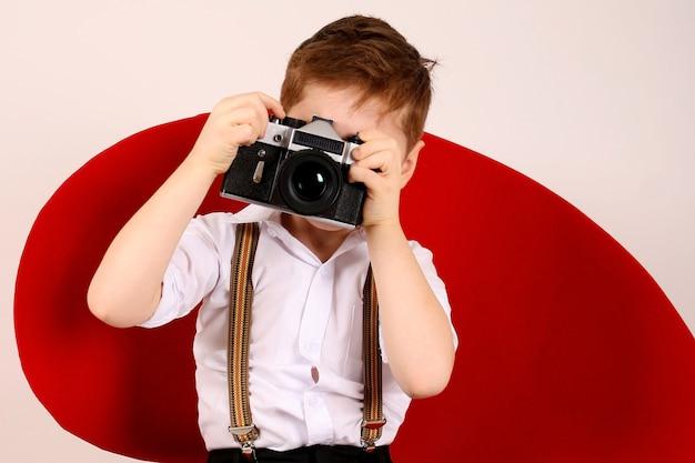 Garotinho fotógrafo em cadeira vermelha de estúdio com câmera de filme